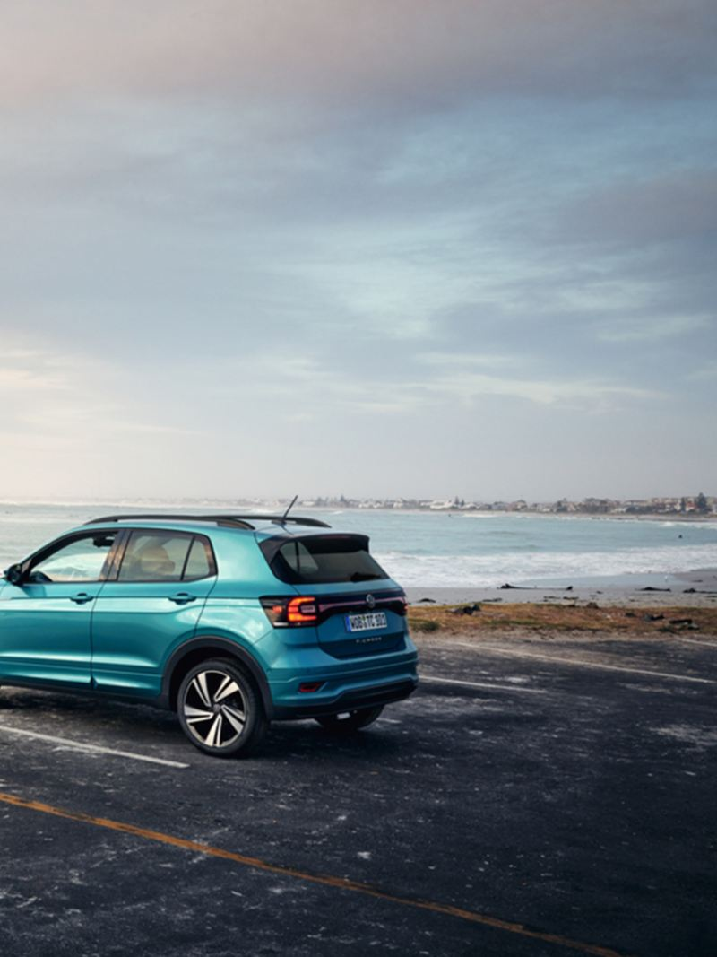 New VW T-Cross on asphalted parking lot on coast with stony beach