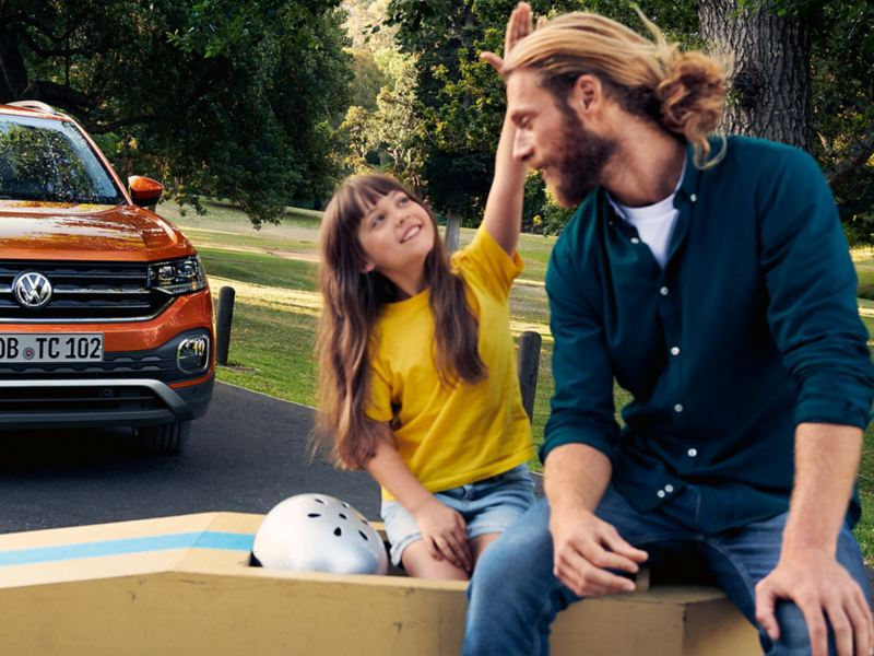 Man and girl sitting in front of a VW