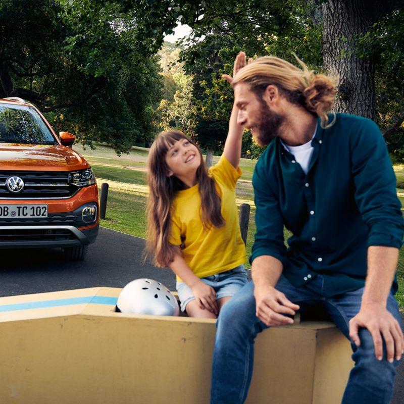 Vater und Tochter mit Helm neben sich sitzen auf einer Seifenkiste, im Hintergrund ein VW T-Cross