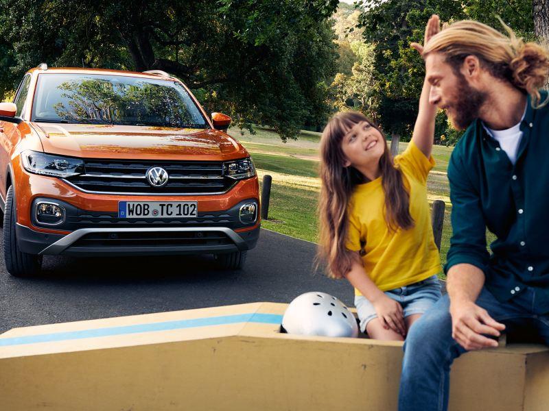 En jente og mann sitter på en olabil foran Volkswagen T-Cross SUV