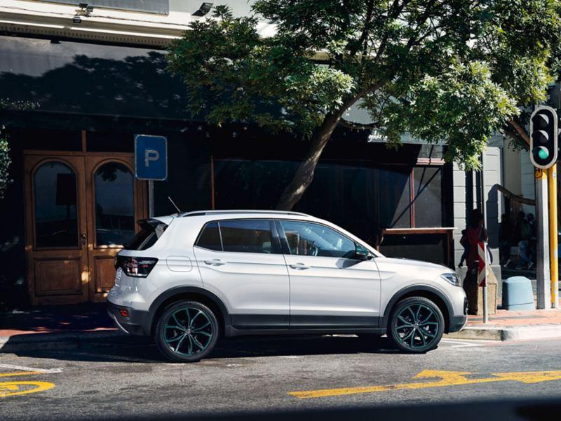 """VW T-Cross mit Designpaket """"Bambus Garden Green"""" parkt nahe einer Kreuzung mit Ampel"""