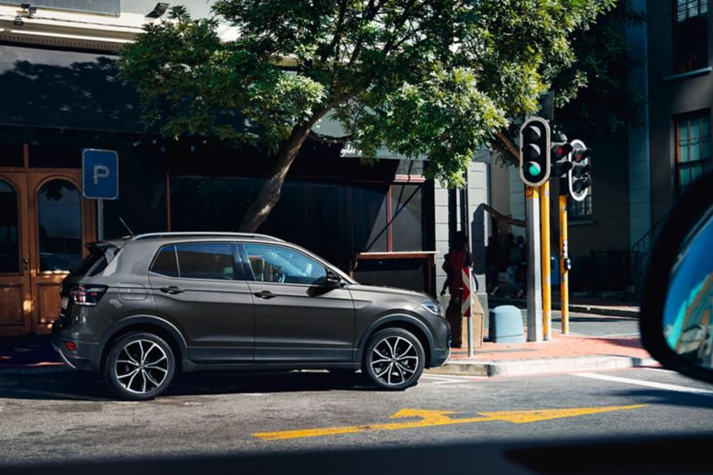 "VW T-Cross with design package ""Black"" parks near a crossing with traffic lights"