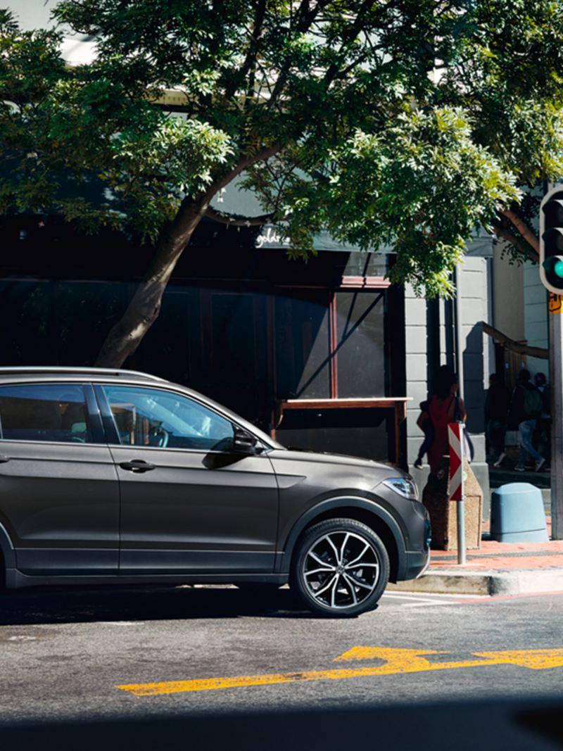 """VW T-Cross mit Designpaket """"Schwarz"""" parkt nahe einer Kreuzung mit Ampel"""