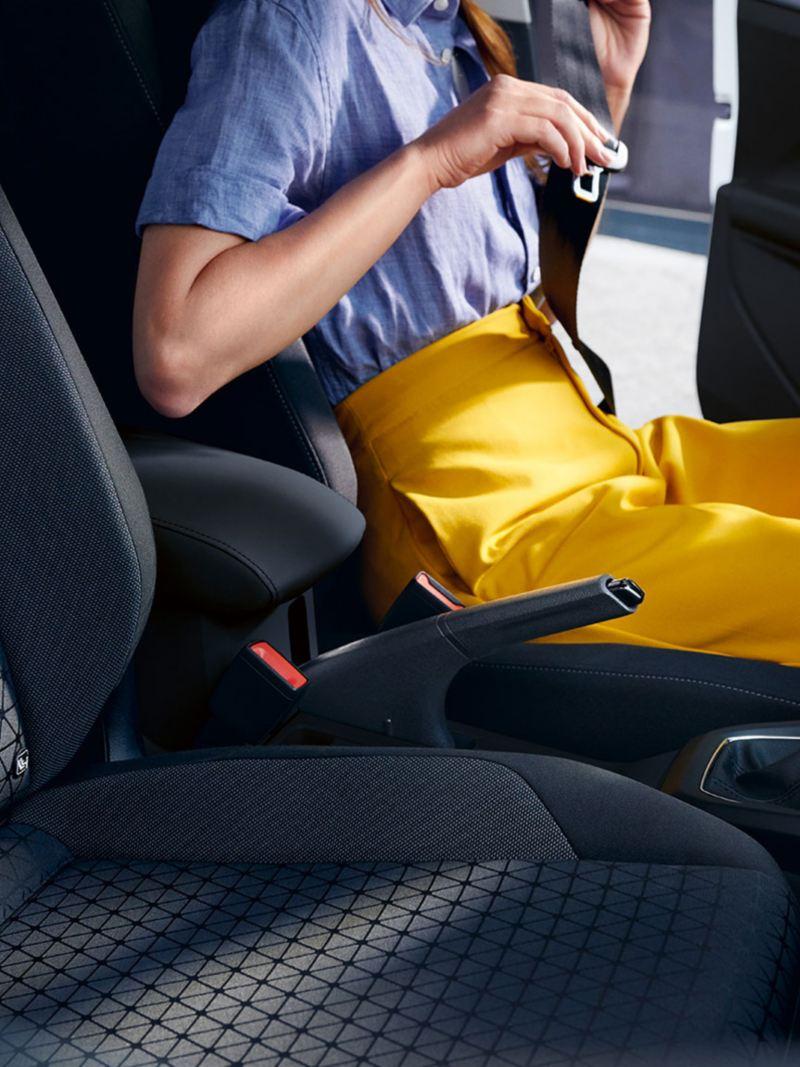 Frau auf Fahrersitz des VW T-Cross schnallt sich an; Kopf nicht im Bild