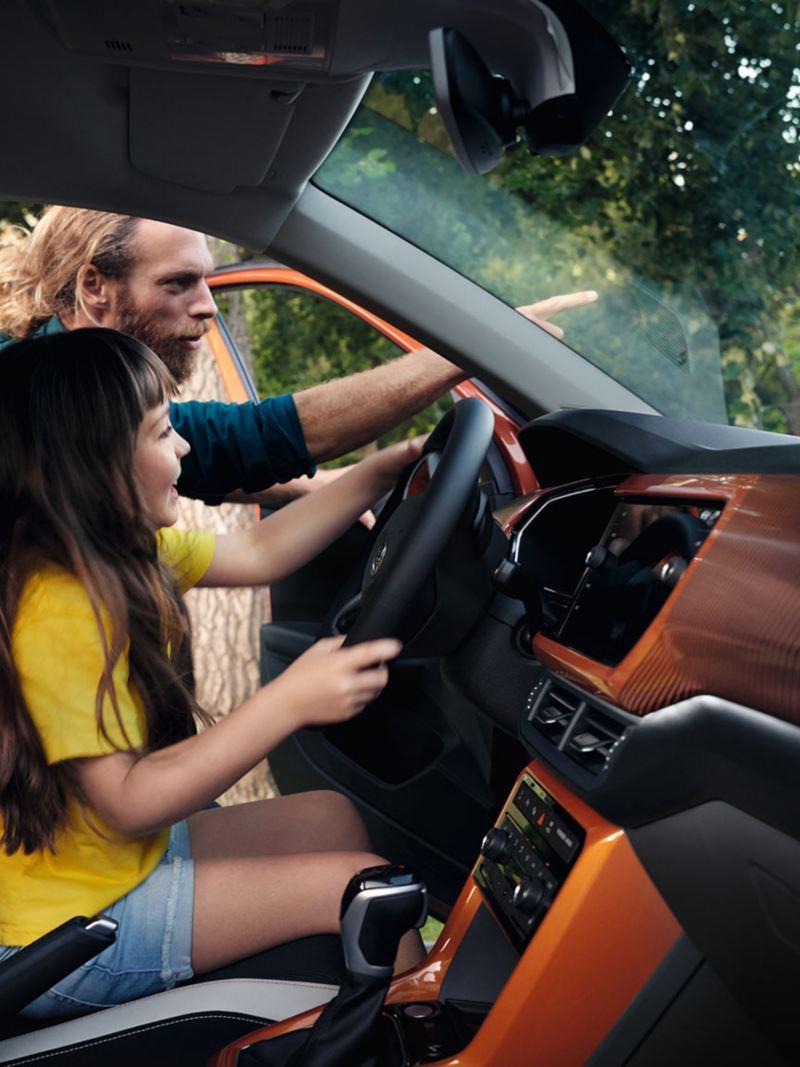 Women sitting inside VW T-Cross looking at mobile phone
