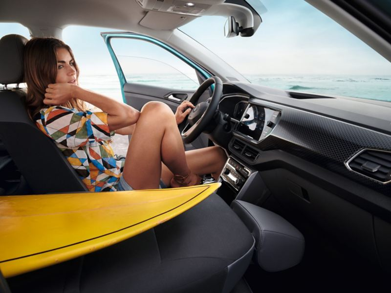 Woman sits relaxed in the driver's seat, the driver's door is open, the passenger seat, on which the tip of a surfboard lies, folded down.