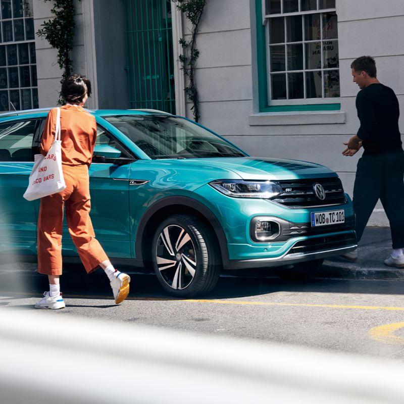 Mann und Frau steigen in einen VW T-Cross ein