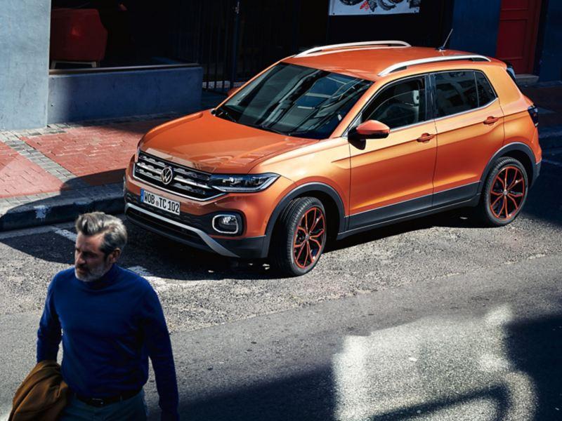 En mann går forbi Volkswagen T-Cross SUV