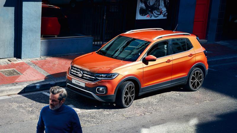 Volkswagen T-Cross parcheggiata su una strada di città, in parte all'ombra, in primo piano un uomo che cammina