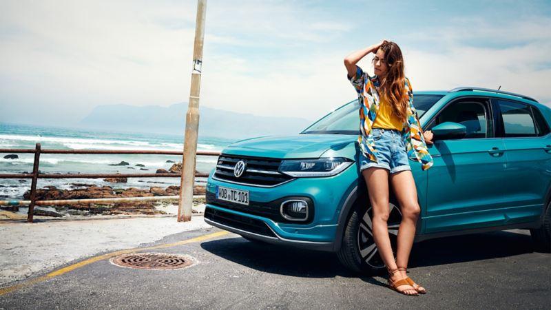 Ragazza appoggiata a una VW T-Cross parcheggiata lungo una costa rocciosa su strada asfaltata