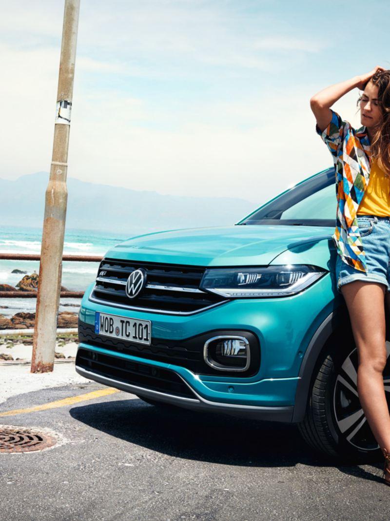 Kvinna lutar sig mot en VW T-Cross invid en strand.