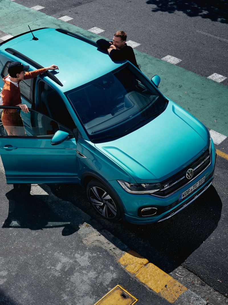 Man and woman at front doors of a parked new VW T-Cross