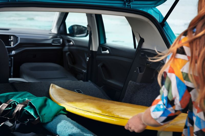 Woman with colourful blouse stowed surfboard in VW T-Cross, for which passenger seat was folded down