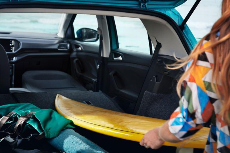 Kvinna lyfter en surfbräda ut ur bagageutrymmet på en VW T-Cross.
