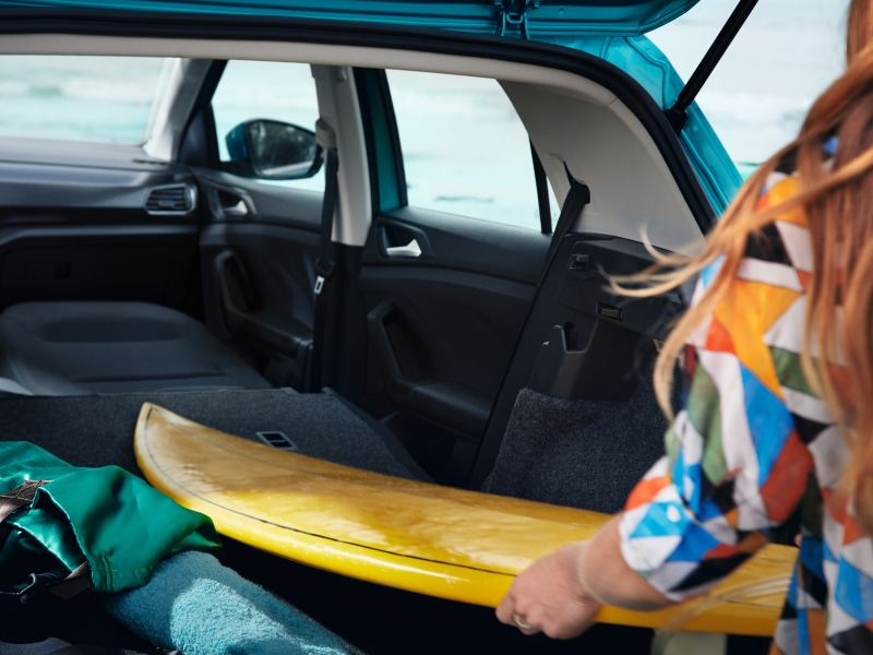 Frau mit bunter Bluse verstaut Surfbrett im VW T-Cross, wofür Beifahrersitz umgeklappt wurde