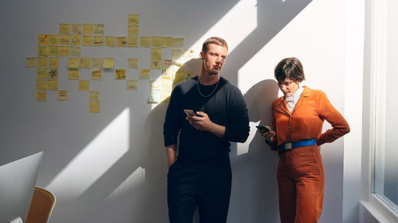 Mann und Frau mit Smartphone lehnen an einer Wand
