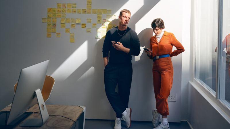 Mann und Frau lehnen an Wand und konfigurieren Ihren Volkswagen am Smartphone