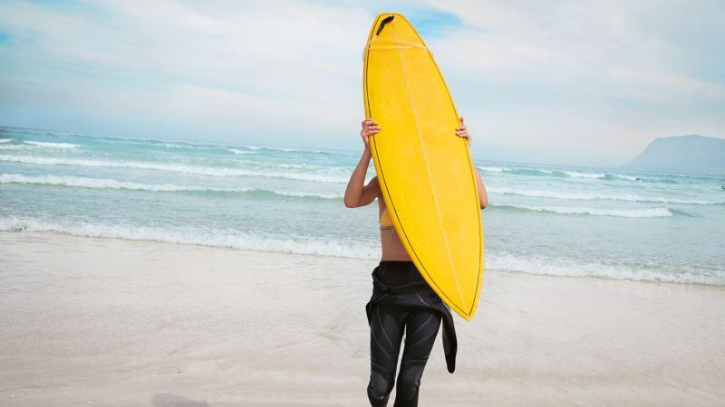 Kvinna bär en surfbräda på en strand.