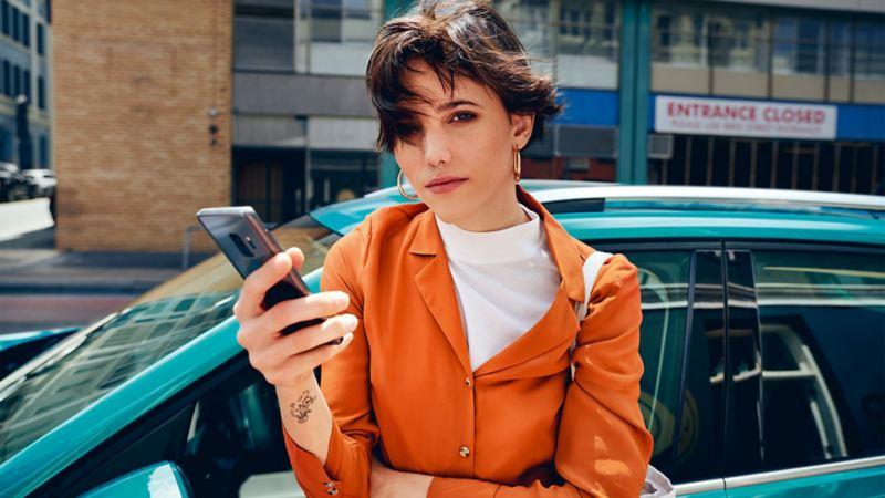 Frau schaut auf ihr Handy, im Hintergrund der T-Cross