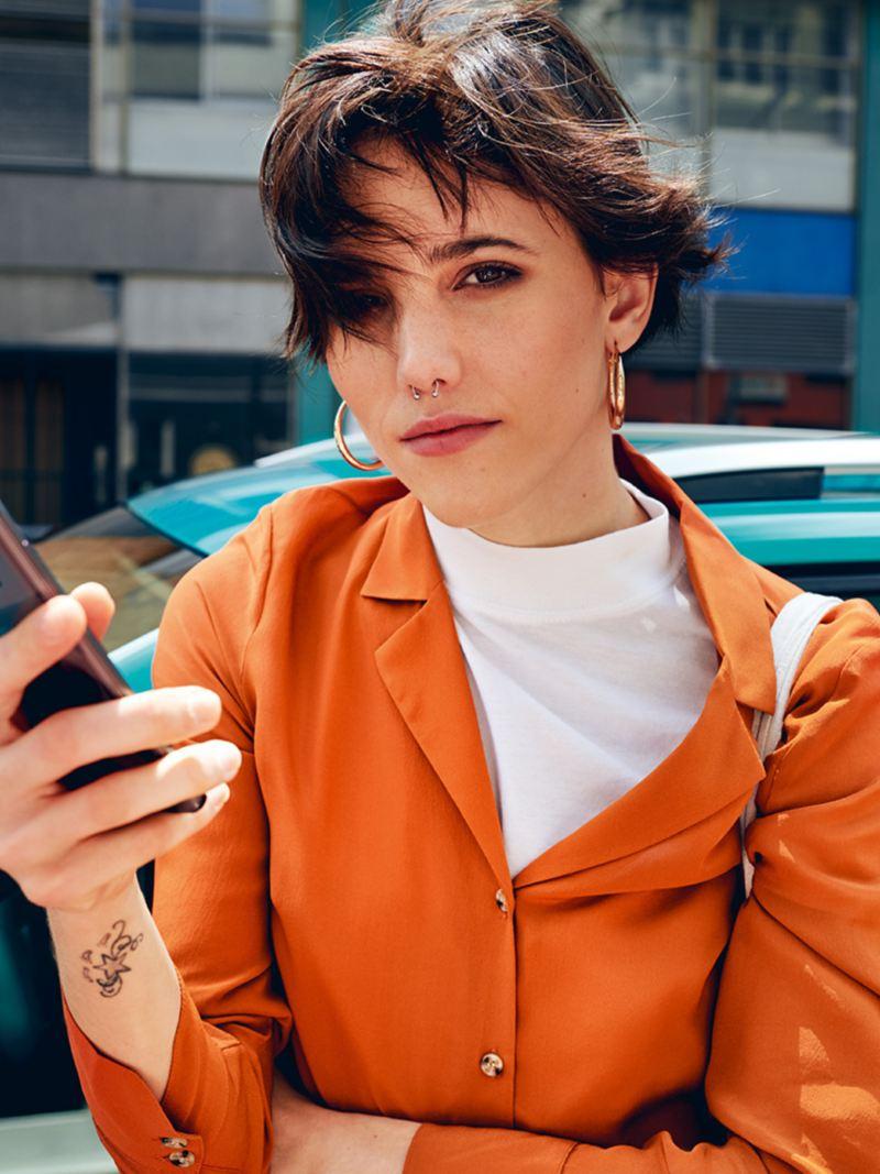 En kvinne står foran Volkswagen T-Cross med mobilen i hånden
