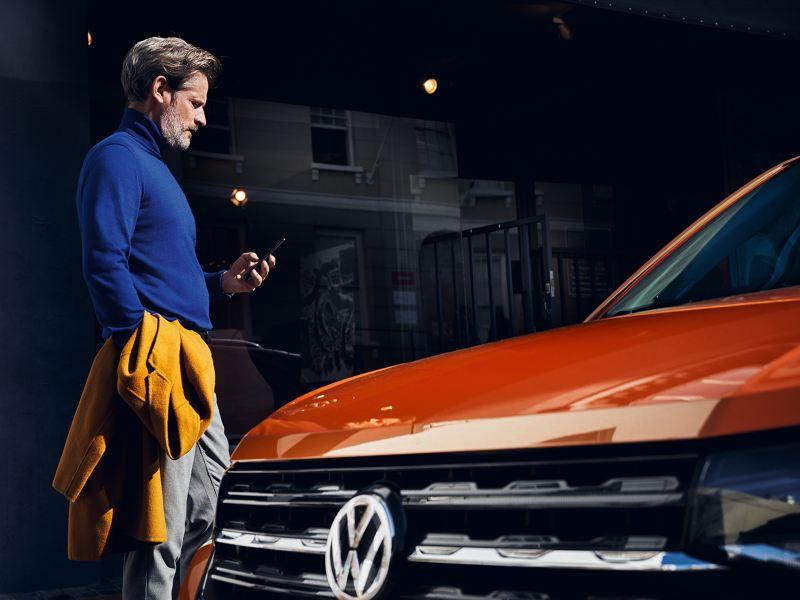 El hombre mira su smartphone, en primer plano su vehículo