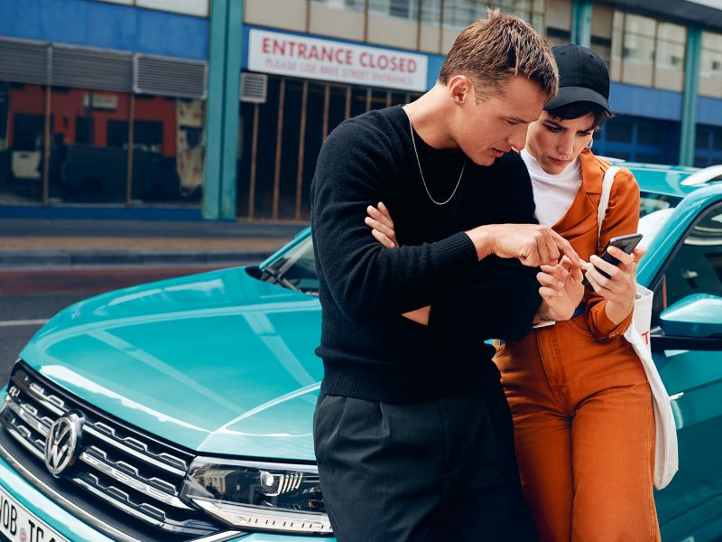 A man and a woman lean on the side of a parked VW T-Cross and look at a cell phone together