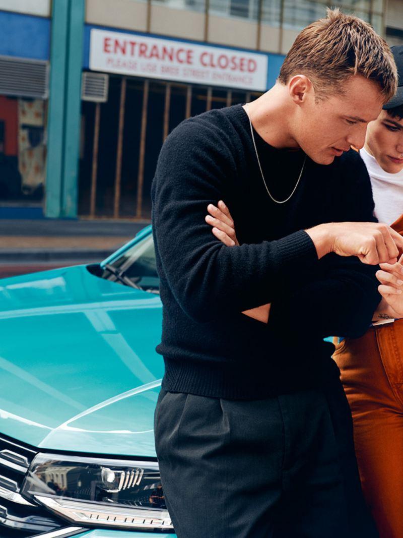 Mies ja nainen seisovat Volkswagen T-Crossin edessä ja selaavat matkapuhelinta