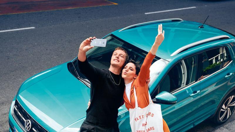 Ein Paar macht ein Selfie vor dem T-Cross