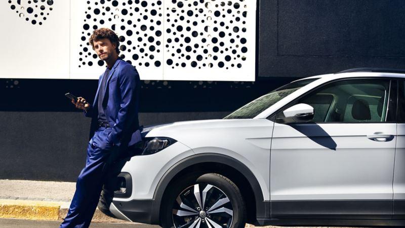 Mann lehnt am Volkswagen und hält sein Smartphone in der Hand