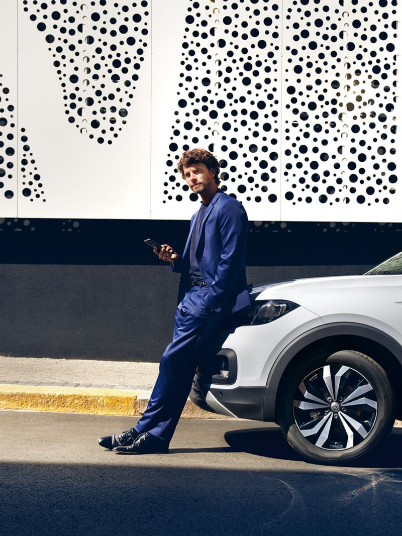 A man leans on a parked car and looks at his smartphone