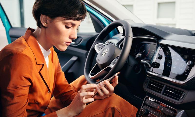 Frau im Volkswagen tippt in ihr Smartphone
