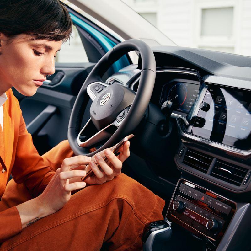 Junge Frau mit Handy im VW T-Cross Innenraum