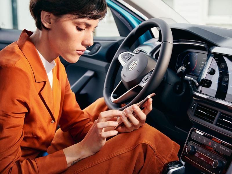 Una donna, seduta al posto di guida della sua auto Volkswagen parcheggiata, consulta il suo smartphone.