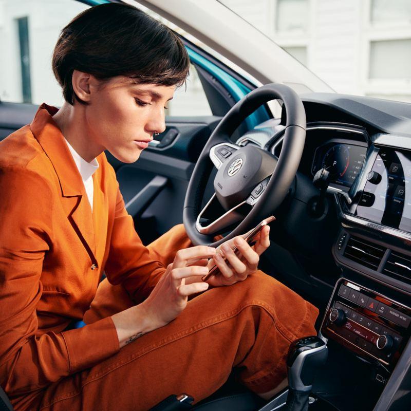 Frau in einem VW T-Cross mit Handy in der Hand und geöffneter Tür
