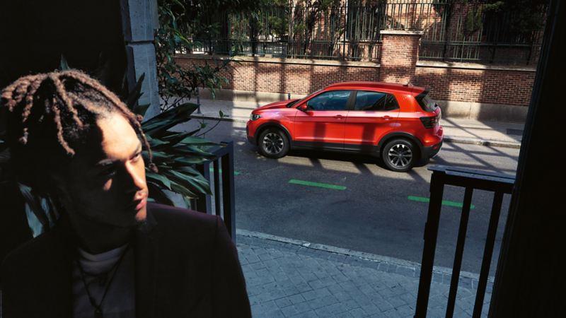 Punainen Volkswagen T-Cross kuvattuna sivulta kadulla parkissa