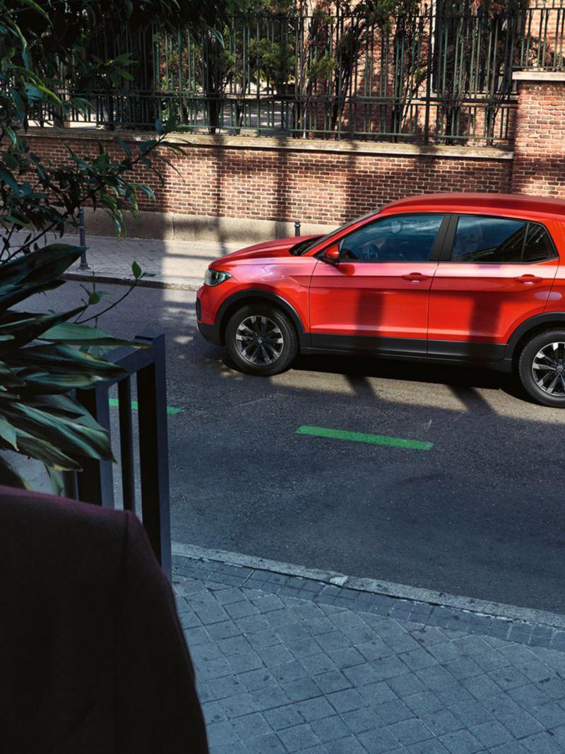 VW T-Cross laterale rossa parcheggiata in una via