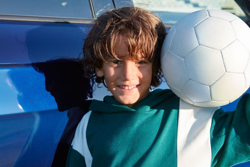 Boy with ball next to his face in front of VW T-Cross UNITED