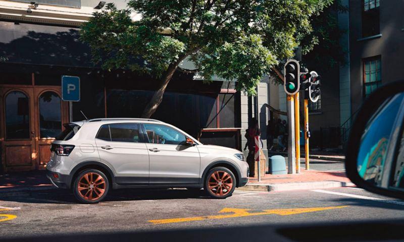 """Volkswagen T-Cross com pacote design """"Penny Copper"""" estacionado perto de um cruzamento com um semáforo"""