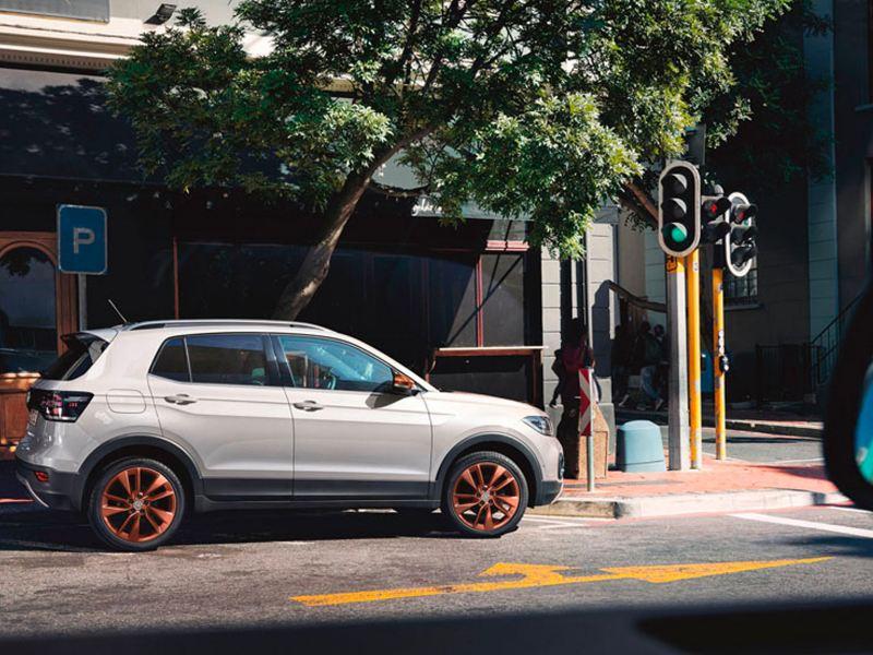 "VW T-Cross mit Designpaket ""Penny Copper"" parkt nahe einer Kreuzung mit Ampel"