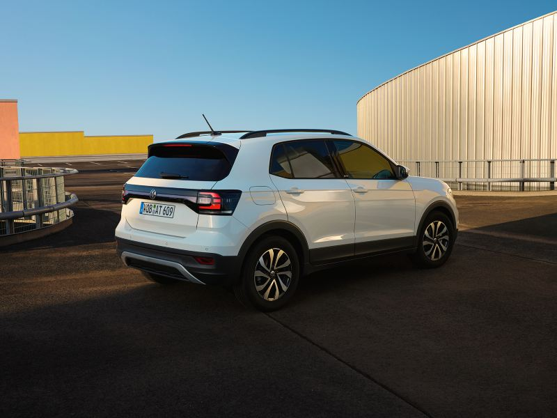 Weißer VW T-Cross ACTIVE steht in urbaner Umgebung vor blauem Himmel. Blick auf Kofferaum und Seite.