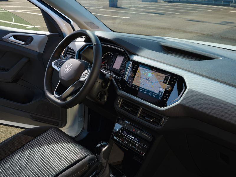 Weißer VW T-Cross ACTIVE von innen. Cockpit mit Multifunktionslenkrad, Pedalkappen und Armaturen mit Ambientebeleuchtung.