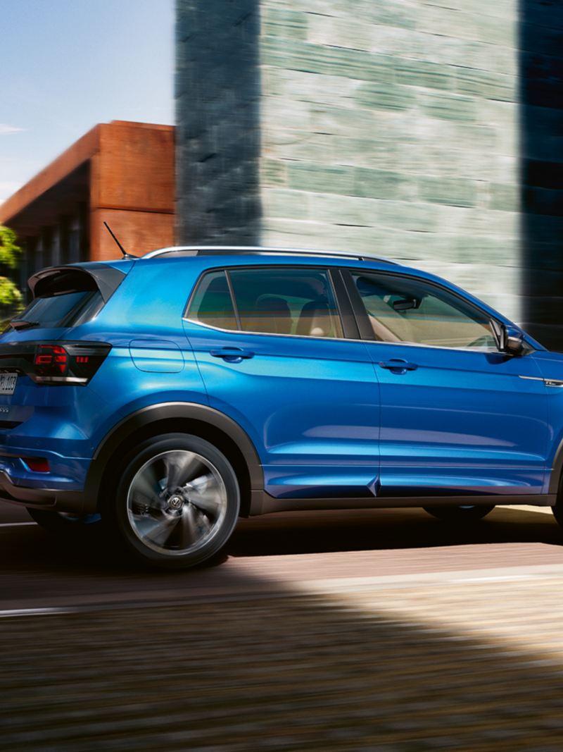 Sininen Volkswagen T-Cross ajaa kaupungin kadulla, auto on kuvattu sivustapäin