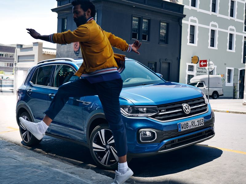 A man is standing in front of a blue VW T-Cross