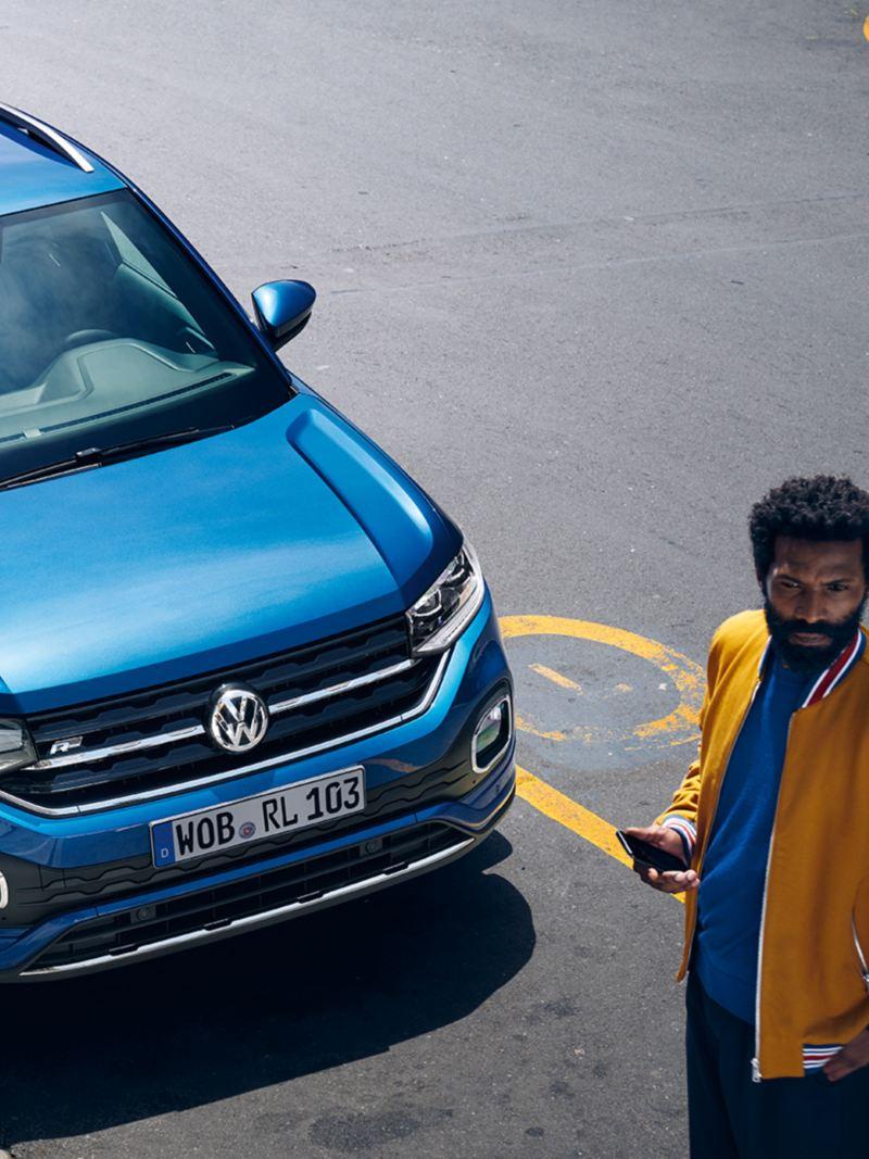 Homem com smartphone diante de um T-Cross