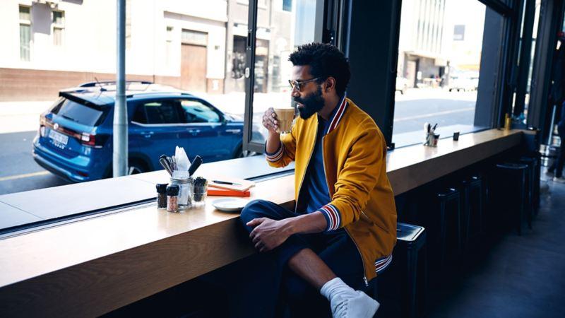 Mann sitzt im Café und sieht auf sein Auto – Probefahrten-Schutz