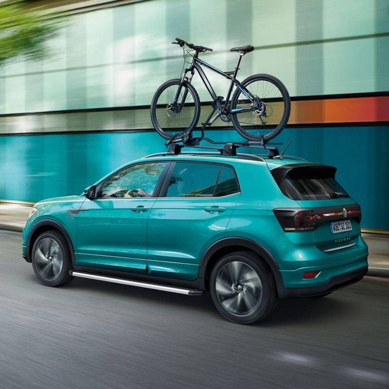 Ein türkiser Volkswagen T-Roc mit VW Zubehör Fahrradträger fährt auf einer Straße