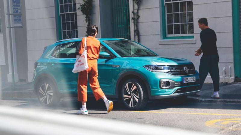 Una pareja caminando hacia un Volkswagen T-Cross esmeralda aparcado en la calle