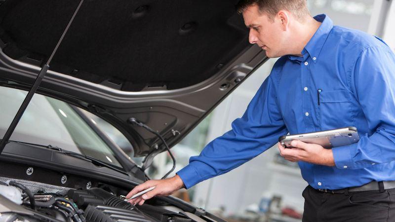 Technical expert examining van engine