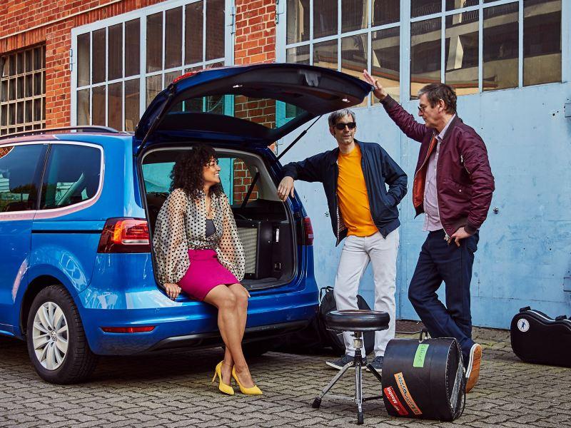 Frau sitzt entspannt im geöffneten Heck eines VW Touran und unterhält sich mit zwei Männern