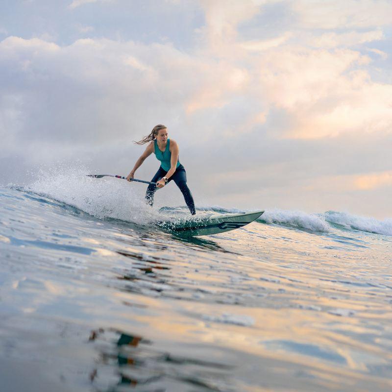 Eine Frau surft mit ihrem Board im Meer